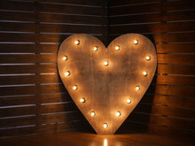 Wooden Heart With Light Bulbs On The Contour On The Background Of Wooden Boards. In The Studio. Horizontally