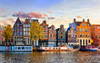 canvas print picture - Amsterdam Netherlands dancing houses over river Amstel landmark in old european city spring landscape.