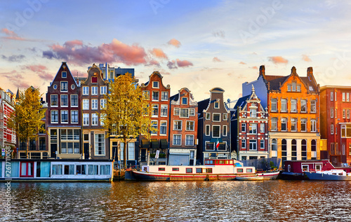 Photo Stands Blue sky Amsterdam Netherlands dancing houses over river Amstel landmark in old european city spring landscape.