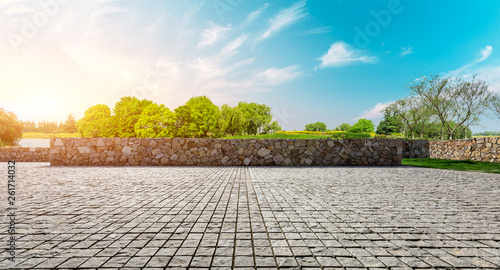 Photo Stands Trees Rough square stone floor and green woods with sky background