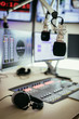 Radio broadcasting studio: Microphone in the foreground, modern studio in the blurry background