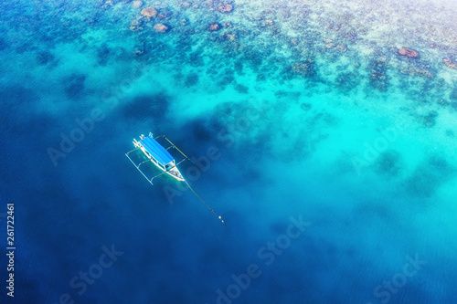Photo Stands Shipwreck Boat on the water surface from top view. Turquoise water background from top view. Summer seascape from air. Gili Meno island, Indonesia. Travel - image