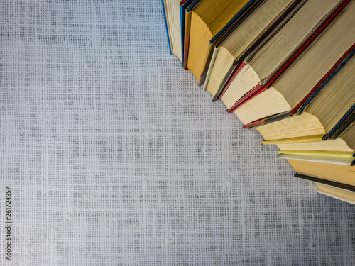 Vintage books stacked side by side framing open white fabric background for copy Tablou Canvas
