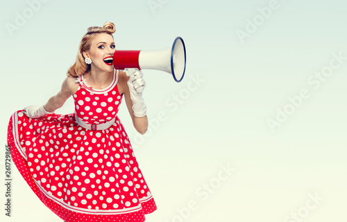 happy woman holding megaphone, dressed in pin-up style red dress Tableau sur Toile