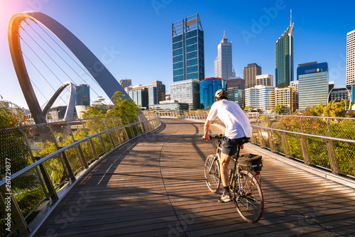 A man cycling on an elizabeth bridge in Perth city