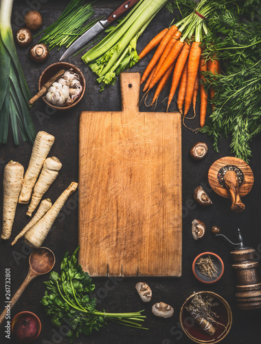 Valokuva  Food background with cutting board and various organic farm vegetables on dark rustic table with kitchen utensils, herbs and spices, top view