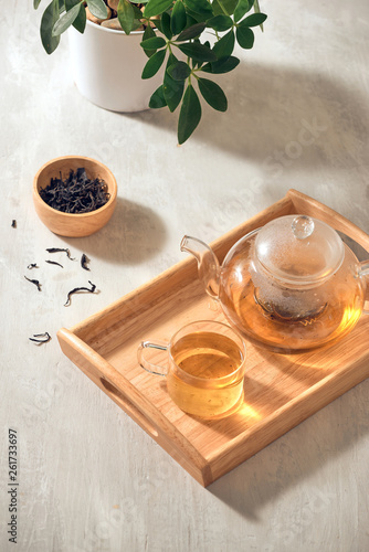 Stickers pour porte Pierre, Sable Tea in a transparent cup and teapot on a wooden background