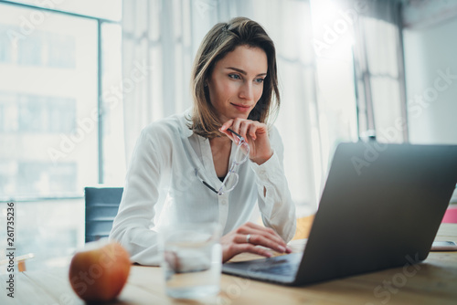 фотографія Confident businesswoman working on laptop at her workplace at modern office