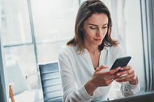Young Business Woman Using Mobile Mobile Phone At Her Workplace At Modern Office .Blurred Background