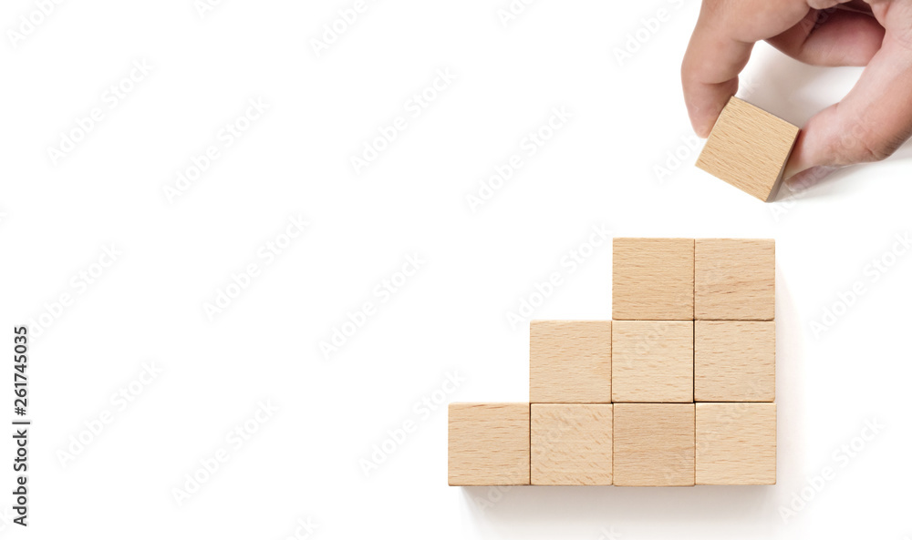 Fototapeta Hand arranging wooden block stacking as step stair on whith background. Business concept for growth success process. Copy space