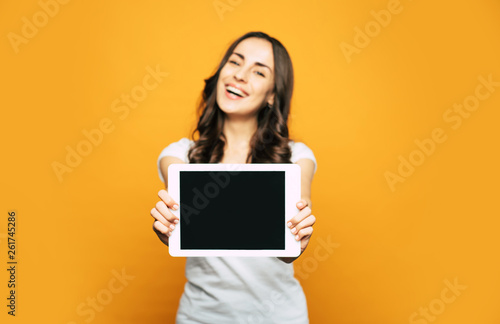 Photo  A screen of a white tablet PC which is placed in hands of  a nice and happy woman with pleasant appearance and cool casual outfit