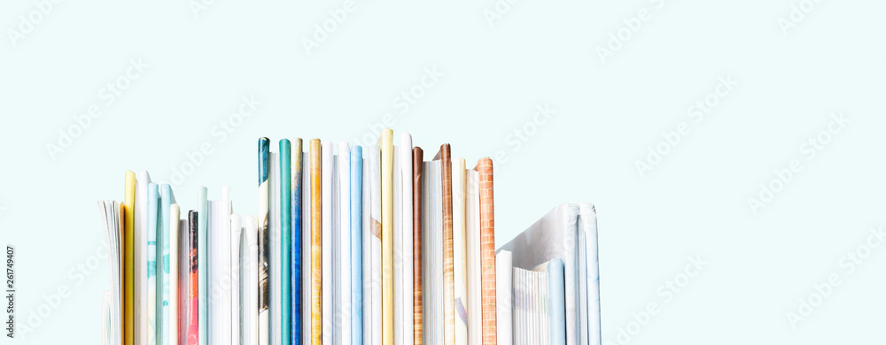 Fototapeta Close view of Stack of children's books on a pastel blue background. Long wide banner with copy space.