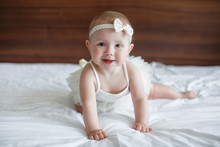 Baby Girl Crawling On Bed And Laughing. Happy Healthy Little Child At Home. Infant Kid In Sunny Nursery.A Child Of 5 Months Is Having Fun Alone,sitting On A Snow-white Bed.