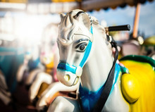 Fairground Carousel Or Merry-go-round Horses In Soft Summer Light.