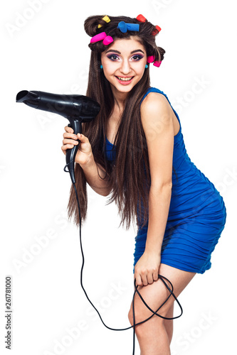 cute cheerful young girl in blue dress with hair curlers in her hair and with hairdryer in her hand.