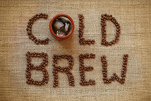 A Cup Of Cold Brewed Coffee With Coffee Beans On Burlap Background