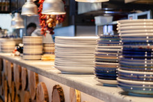 Closeup Stack White And Colored Blue Porcelain Plates With Oriental And Ethnic Ornament Stands In Open Kitchen Of Trendy Restaurant. Concept Washing Dishes, Preparing For Lunch, Evening Service