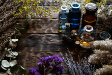 Various Dried Herbs And An Essential Oil Bottles On A Brown Wooden Board Background. Herbal Medicine.