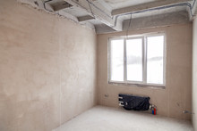 Empty Room With A Window And A Battery In A House Under Construction, Plastered Walls, A Screed On The Floor, Concrete Multi-level Slabs. Concept Of Repair New House, Overhaul, Reconstruction