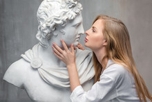 Young Woman Kissing God Apollo Bust Sculpture. Ancient Greek God Of Sun And Poetry Plaster Copy Of A Marble Statue On Grange Concrete Wall Background. Ancient Art And Living Beauty