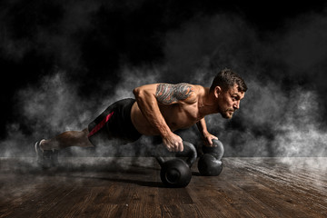 Fototapeta Fitness / Siłownia Muscular man doing pushups on kettle ball