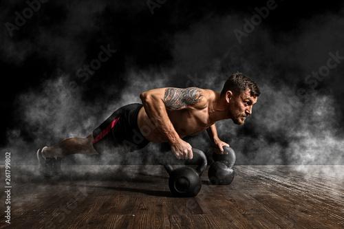 Fotografia  Muscular man doing pushups on kettle ball