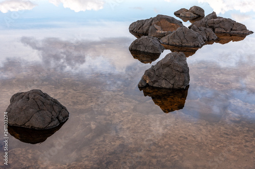 Fényképezés  Stones in shallow water and reflection of the sky with clouds in the water
