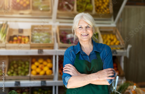 Obraz na płótnie Portrait of confident owner with arms crossed standing in small grocery store