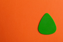 Green Guitar Pick On Color Bac...