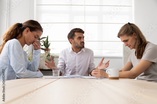 Angry mean male boss shouting criticizing stressed sad female employees Canvas Print