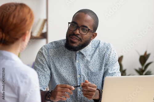 Fototapeta African hr manager listening to caucasian applicant at job interview obraz