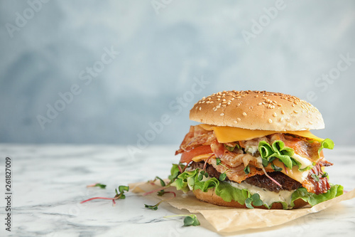 Fototapeta Tasty burger with bacon on table against color background. Space for text obraz