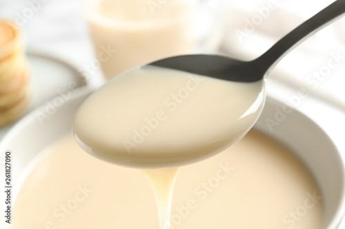 Spoon of pouring condensed milk over bowl, closeup. Dairy products