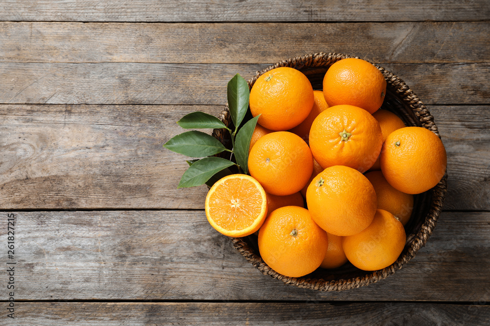 Fototapety, obrazy: Wicker bowl with ripe oranges on wooden background, top view. Space for text