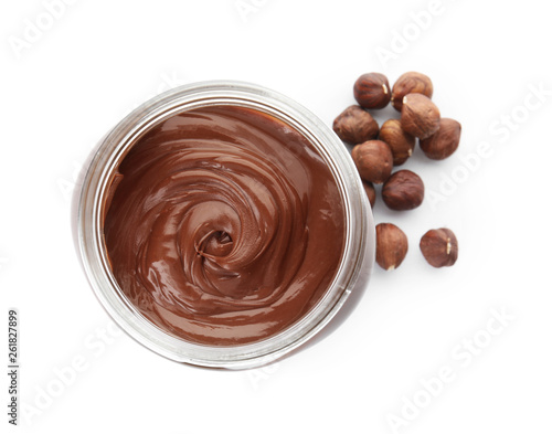 Fotografia Glass jar with tasty chocolate cream and hazelnuts isolated on white, top view