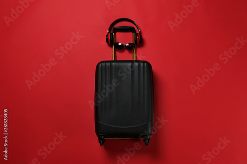 Fototapety, obrazy: Stylish suitcase with sunglasses and headphones on color background, top view