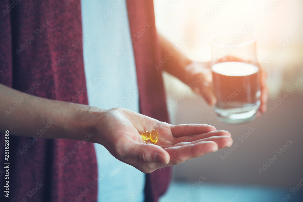 Fototapety, obrazy: young woman taking pills, golden fish oil capsule, omega-3 supply, health care, morning sunshine background