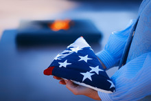 Happy Memorial Day. A Girl Holds A Folded American Flag In Her Hands, Amid A Blazing Fire Of Memory. Concept For Holidays Of The United States Of America.