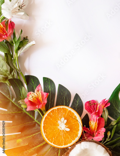 Summer tropical theme background or template with a space for a text, various fruits, green leaves and flowers. Bright summer background