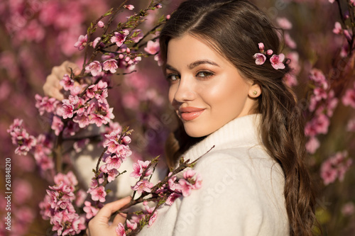 Pretty smiling teen girl posing near blossom cherry tree with pink flowers.