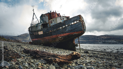 Photo Stands Shipwreck Ship wreck on the beach at low tide. The Old Boat of Corpach, Ben Navis on Loch Eil near Fort William in Scotland.