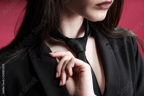 Fotografia  Young beautiful female fashion model in a business stylish suit on a red and black background