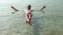 Young Man Swim In The Dead Sea Israel