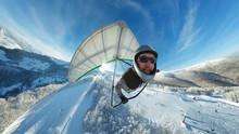 Funny Smiling Hang Glider Pilot Fly Fast Above Winter Ski Resort.
