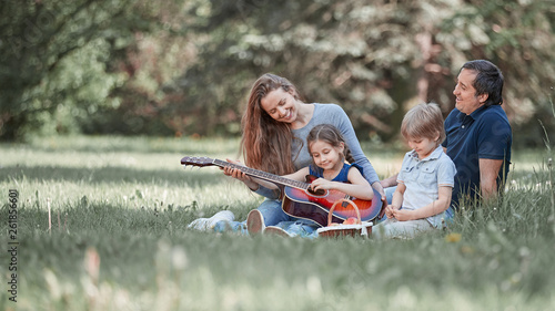 Foto  young family sitting on the grass in a summer Park
