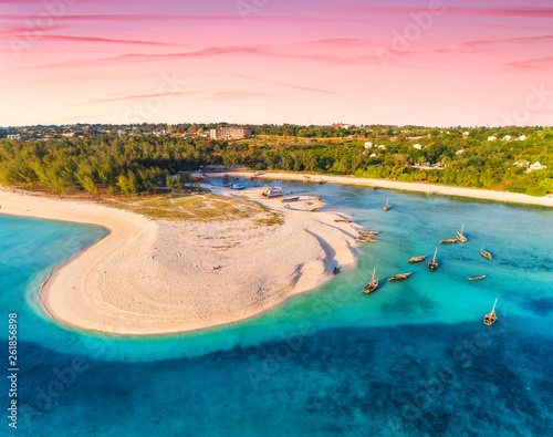 Spoed Fotobehang Zanzibar Aerial view of the fishing boats on tropical sea coast with sandy beach at sunset. Summer holiday. Indian Ocean, Zanzibar, Africa. Landscape with boat, green trees, blue water, colorful sky. Top view