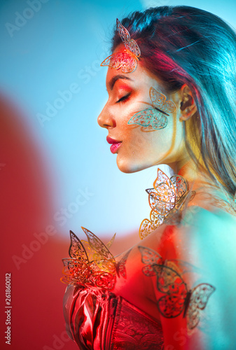 Beauty fantasy model spring girl in colorful bright neon lights. Portrait of beautiful summer young woman in UV. Art design colorful make up with golden butterflies. On colourful vivid background