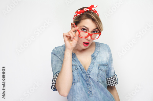 Fotografía  Portrait of attentive beautiful young woman in casual blue denim shirt with makeup and red headband standing holding glasses and looking at camera