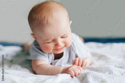 Portrait of crying screaming white Caucasian baby girl boy four months old lying on bed in bedroom on tummy. Natural emotion expression. Childhood lifestyle