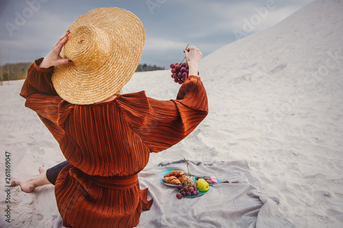 Photographie  Girl sitting on litter and hold a grape in a hand.